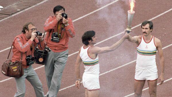 Олимпийский чемпион Сергей Белов (справа) принимает факел с олимпийским огнем из рук трехкратного олимпийского чемпиона Виктора Санеева (слева) - Sputnik Грузия