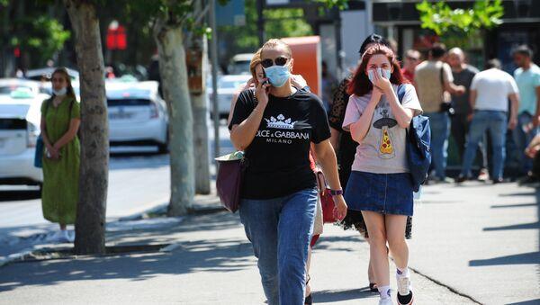 Люди в масках идут по улице - Sputnik Грузия