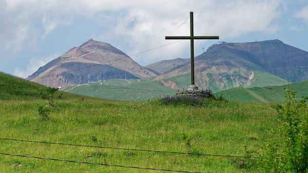 Крест в горах близ Гудаури - на фото видны подъемники горнолыжного курорта - Sputnik Грузия