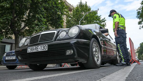 Полицейский проверяет машины из-за пандемии COVID 19 в Баку Азербайджан - Sputnik Грузия