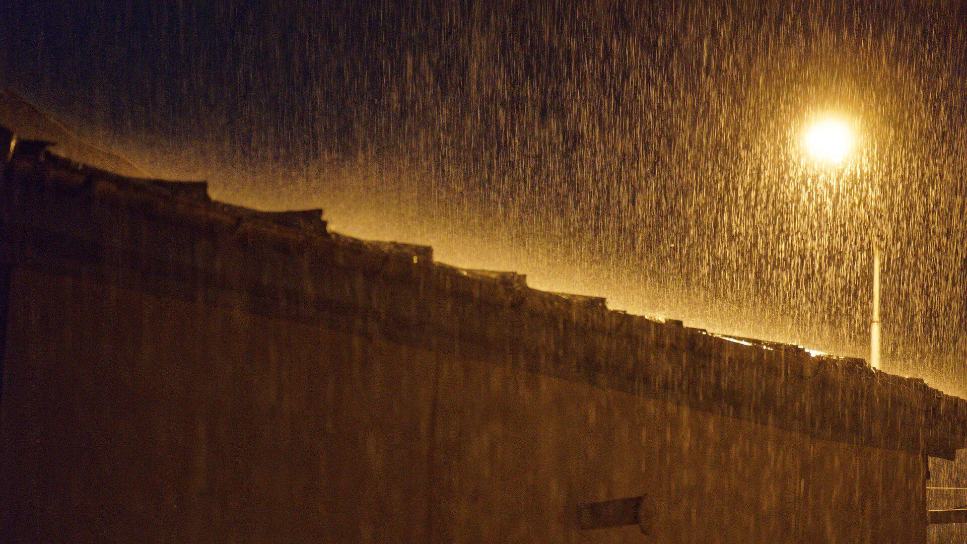 Сильный дождь. Струи воды в свете уличного фонаря - Sputnik Грузия, 1920, 10.09.2021