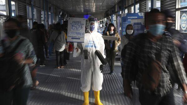 Сотрудник автобусной станции в защитном костюме во время пандемии коронавируса COVID 19 в Джакарте, Индонезия - Sputnik Грузия