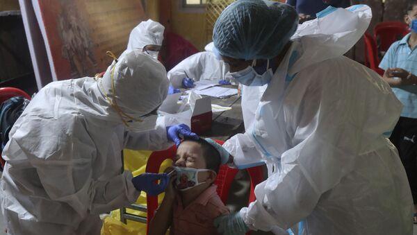 Медики в защитных костюмах оказывают помощь заразившимся во время пандемии коронавируса в Мумбаи, Индия - Sputnik Грузия