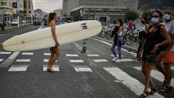 Девушка с доской для серфинга идет по улице Сан-Себастьян в Испании во время пандемии коронавируса COVID 19 - Sputnik Грузия