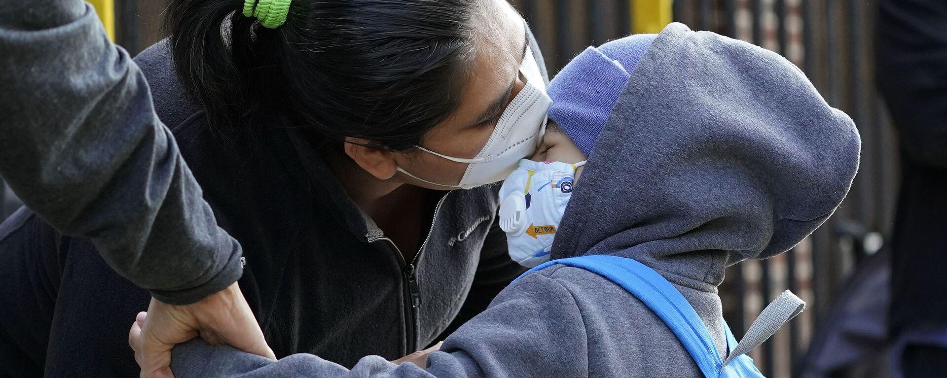 Пандемия коронавируса COVID-19. Мама и дочь в масках целуются в районе Куинс, Нью-Йорк, США перед началом занятий в школе - Sputnik Грузия, 1920, 15.01.2021