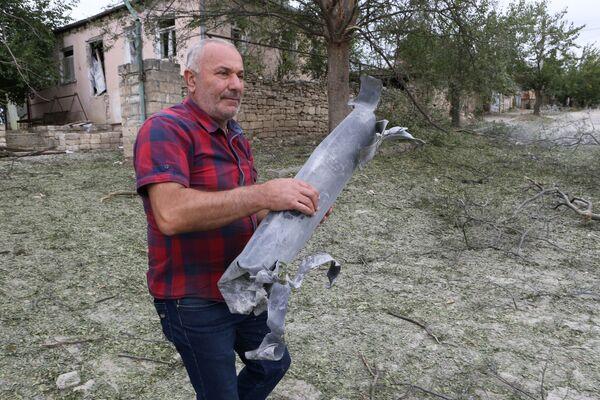Нагорный Карабах. Местный житель показывает разорвавшийся снаряд - Sputnik Грузия