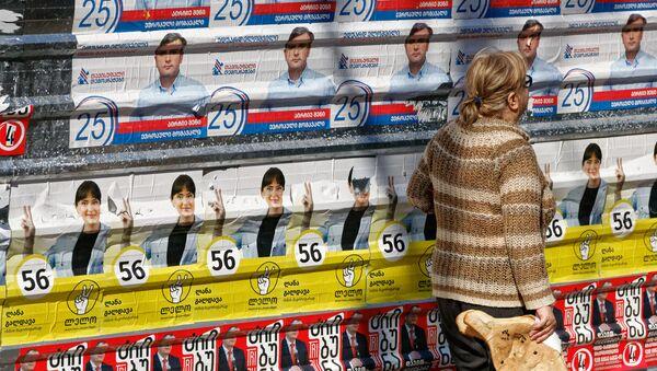 Предвыборная символика и пожилые люди. Женщина идет мимо предвыборных плакатов - Sputnik Грузия