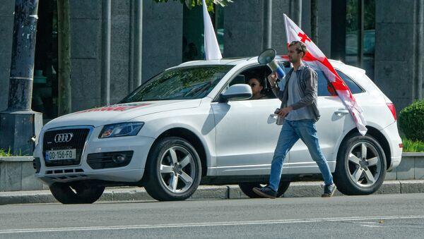 Предвыборная символика и агитация. Человек с мегафоном и машина с флагом Грузии - Sputnik Грузия