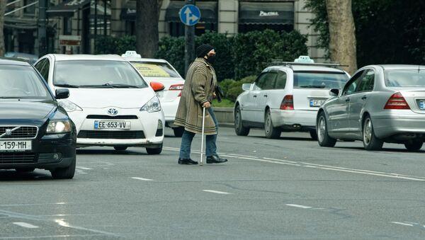 Пешеходы и коронавирус. Пожилая женщина в маске и с палкой переходит улицу в неположенном месте среди машин - Sputnik Грузия