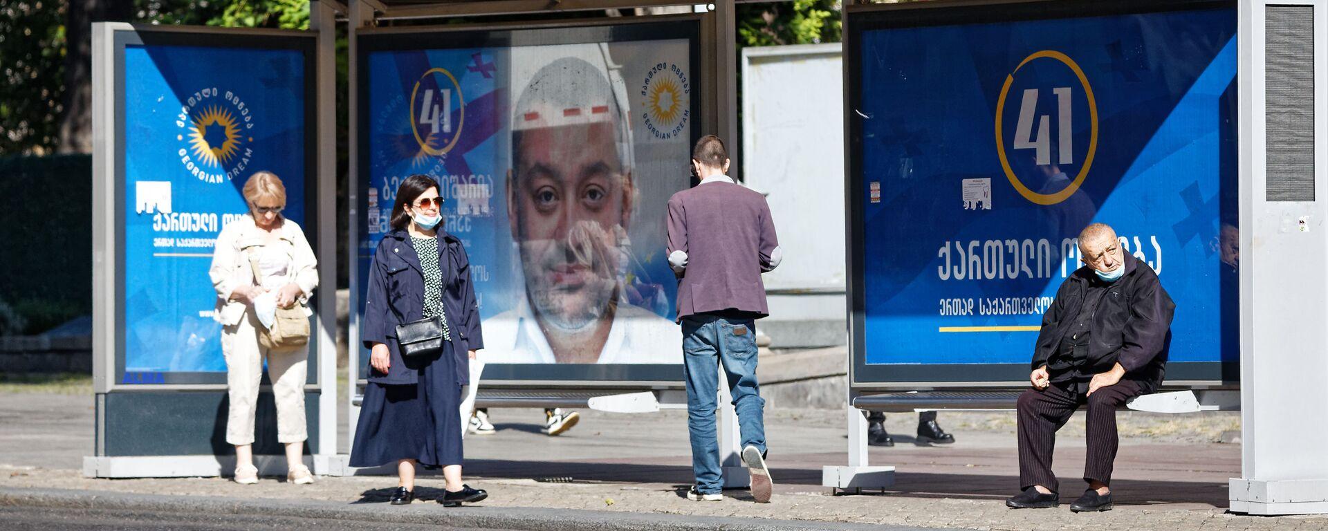 Предвыборная символика и коронавирус. Баннер правящей партии Грузинская мечта на автобусной остановке - Sputnik Грузия, 1920, 30.07.2021
