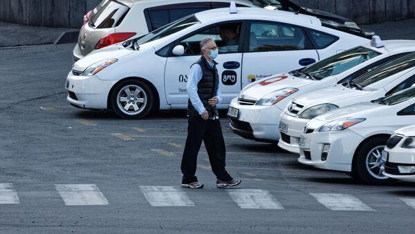 Эпидемия коронавируса - мужчина идет по улице в маске мимо такси - Sputnik Грузия