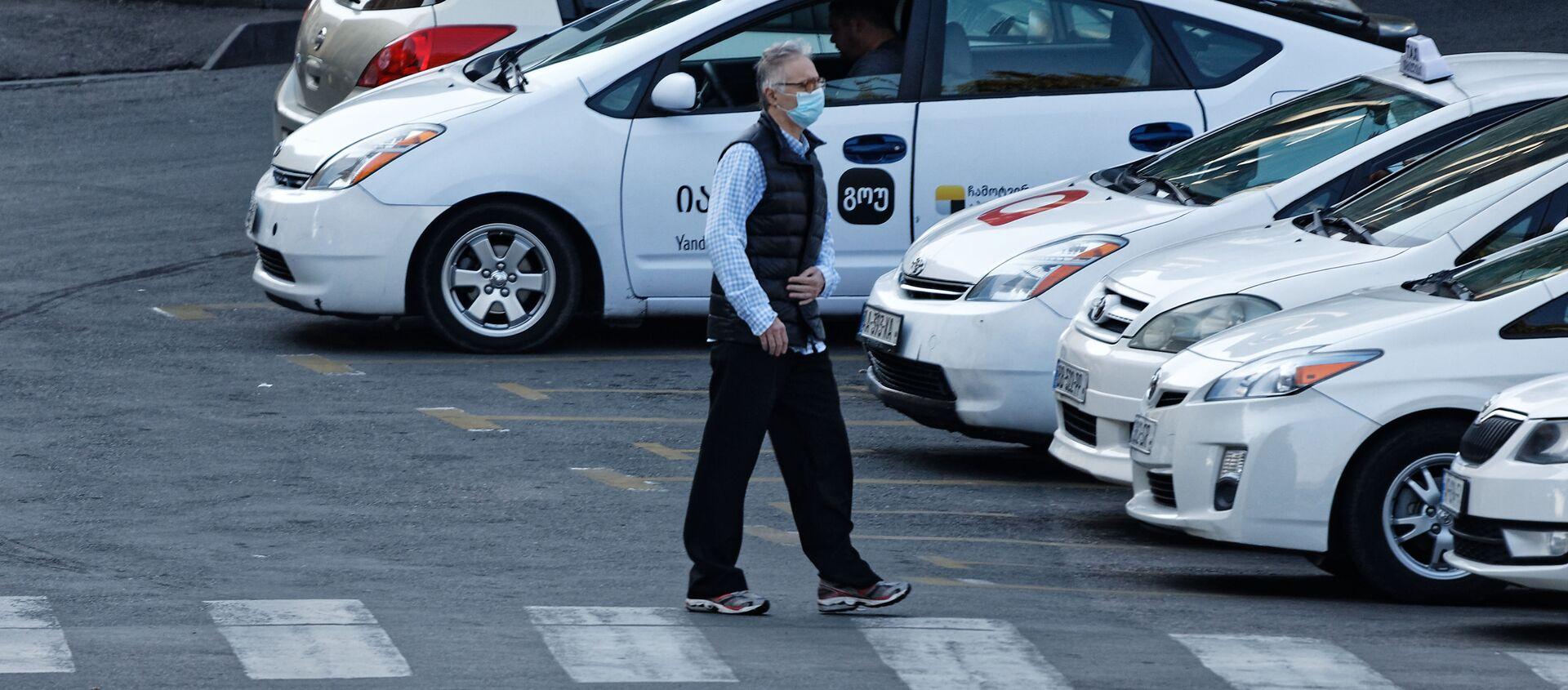 Эпидемия коронавируса - мужчина идет по улице в маске мимо такси - Sputnik Грузия, 1920, 09.02.2021