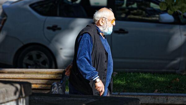 Эпидемия коронавируса - пожилой мужчина на улице в неправильно одетой маске - Sputnik Грузия