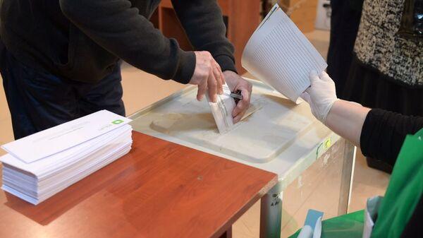 Парламентские выборы в Грузии 2020 - избиратели принимают участие в голосовании. Бюллетень опускают в урну - Sputnik Грузия