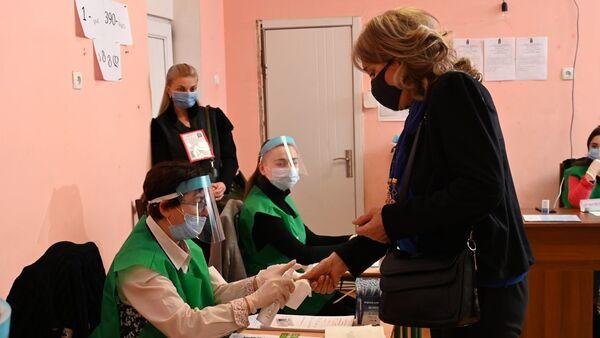 Парламентские выборы в Грузии 2020 - избиратели в масках на участке проходят регистрацию - Sputnik Грузия