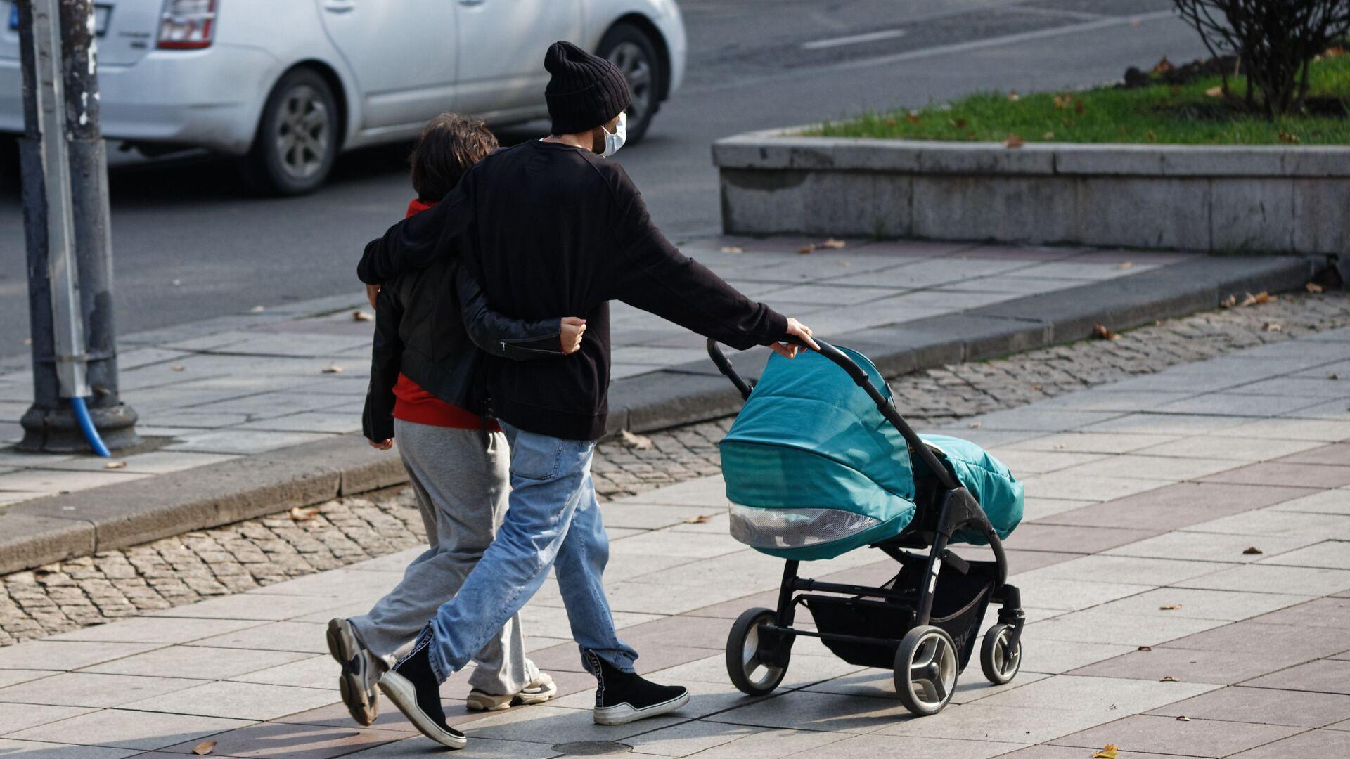 Молодые родители в масках с детской коляской - Sputnik Грузия, 1920, 19.09.2021