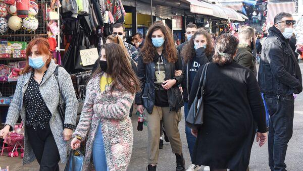 Эпидемия коронавируса. Прохожие в масках идут по территории рынка у вокзала - Sputnik Грузия