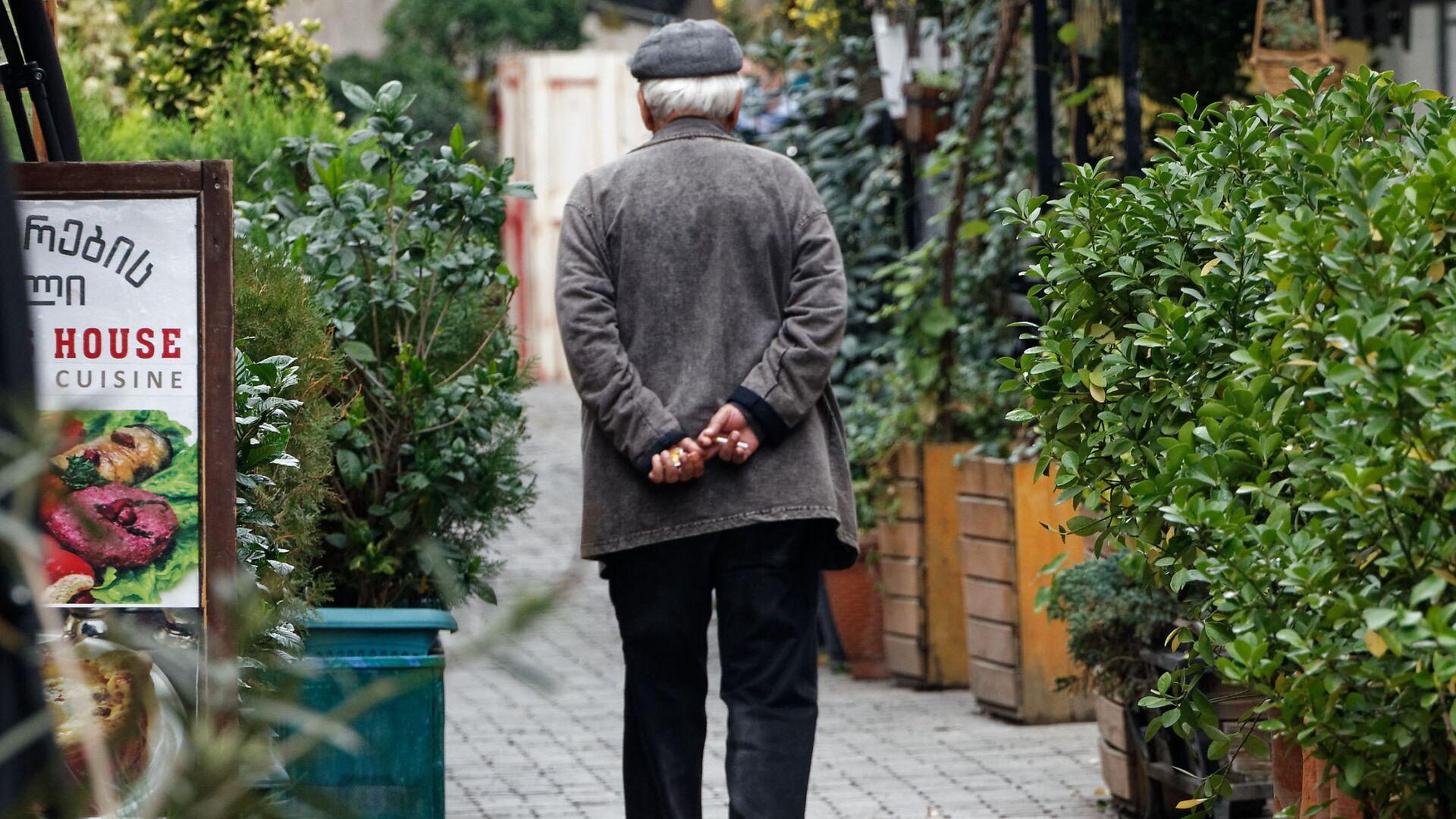 Пенсионер идет по улице мимо закрытых кафе и ресторанов - Sputnik Грузия, 1920, 06.10.2021