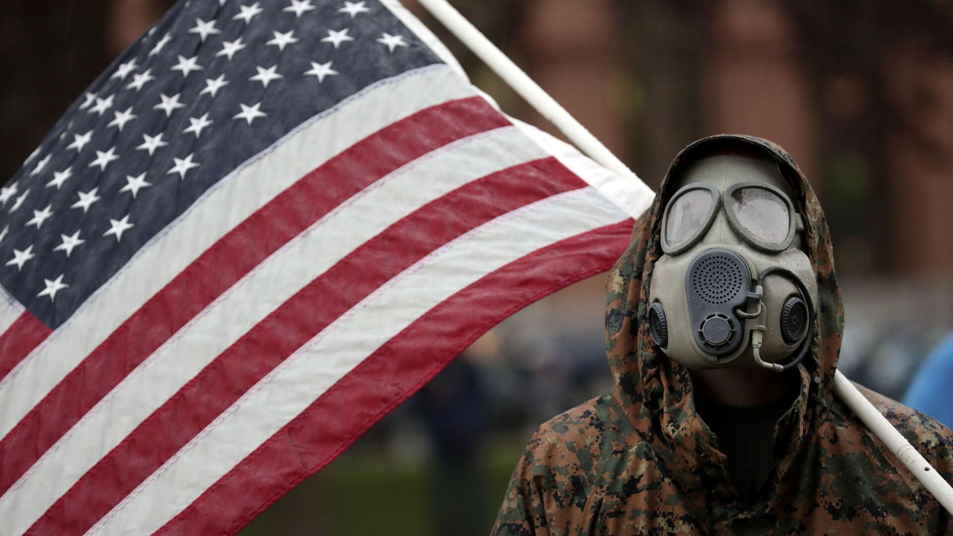 Пандемия коронавируса COVID - 19 - житель США в противогазе с флагом - Sputnik Грузия, 1920, 05.03.2021
