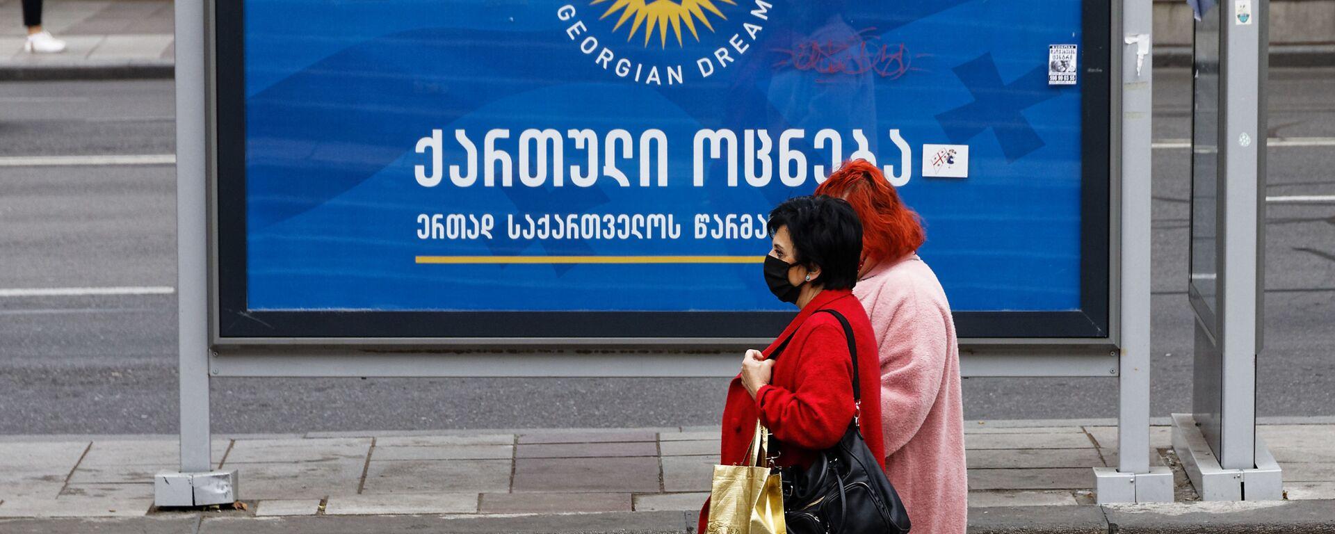 Баннер партии Грузинская мечта - мимо остановки идут женщины в масках защищаясь от коронавируса - Sputnik Грузия, 1920, 19.09.2021