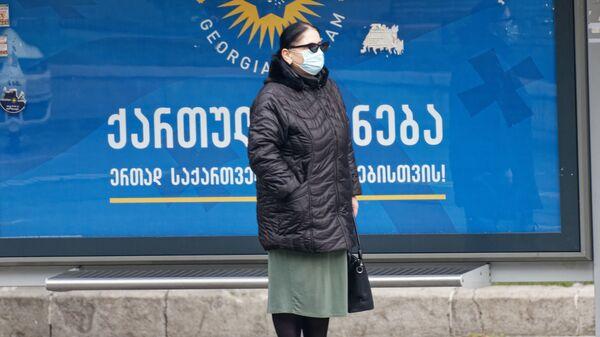 Второй тур выборов - предвыборный баннер партии Грузинская мечта. Женщина на остановке в маске - Sputnik Грузия