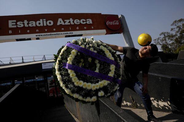 Болельщик у траурного венка во время скорби по Диего Марадоне в Мексике - Sputnik Грузия