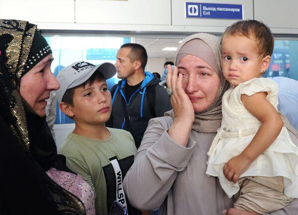 Девочка на руках у своей тети Разет во время встречи в аэропорту Грозного. Пять детей-сирот, вывезенных родителями в Сирию и спасенных при содействии руководства Чечни, доставили в Грозный - Sputnik Грузия