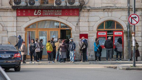 Кутаиси - эпидемия коронавируса. Прохожие в масках в очереди у Liberty Bank - Sputnik Грузия
