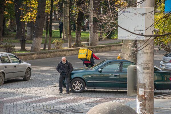 Процветают и службы доставки. На фото - курьер Glovo едет по заказу клиента - Sputnik Грузия