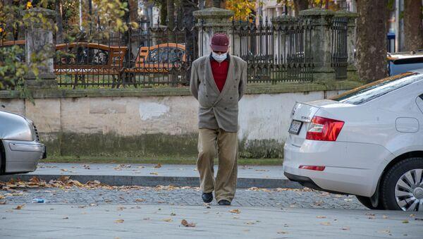 Кутаиси. Эпидемия коронавируса. Пожилой мужчина идет по улице в маске и в очках - Sputnik Грузия