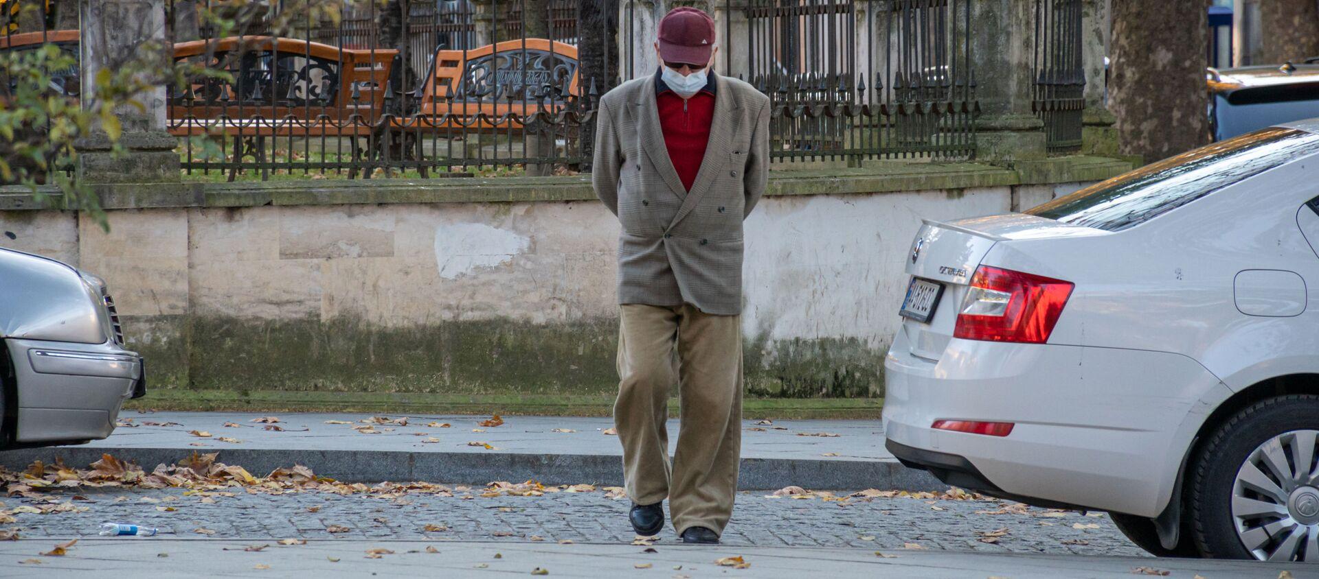 Кутаиси. Эпидемия коронавируса. Пожилой мужчина идет по улице в маске и в очках - Sputnik Грузия, 1920, 01.01.2021
