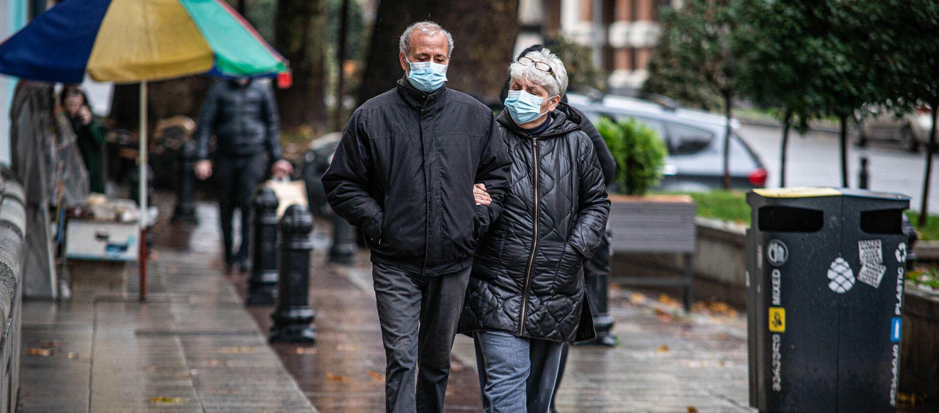 Эпидемия коронавируса - прохожие в масках на улицах грузинской столицы в дождь - Sputnik Грузия, 1920, 31.01.2021