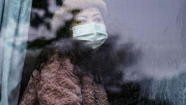 Девушка в маске в автобусе в Ухане, Китай - почти год после начала пандемии  - Sputnik Грузия