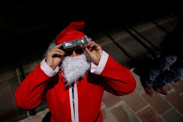 Мужчина в костюме Санта-Клауса в специальных защитных очках наблюдает за солнечным затмением в Патагонии - Sputnik Грузия