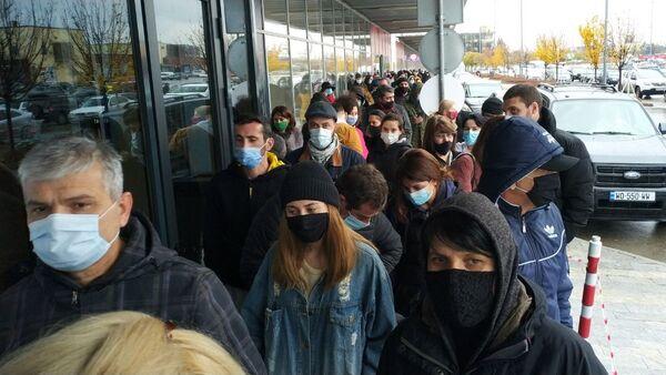 Торговля в магазинах и торговых центрах во время эпидемии коронавируса - люди в очереди в масках - Sputnik Грузия