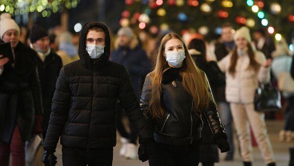 Прохожие в защитных масках на украшенной к Новому Году Красной площади в Москве. - Sputnik Грузия