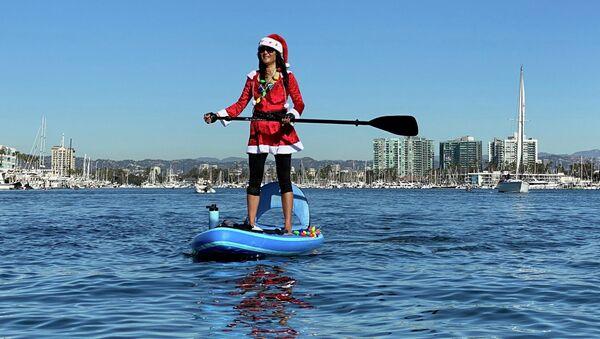 Девушка в костюме Санта-Клауса катается на SUP-серфе в Лос-Анджелесе - Sputnik Грузия