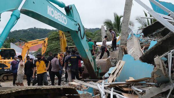 Спасатели ищут выживших среди руин здания, поврежденного в результате землетрясения в Мамуджу, Индонезия - Sputnik Грузия
