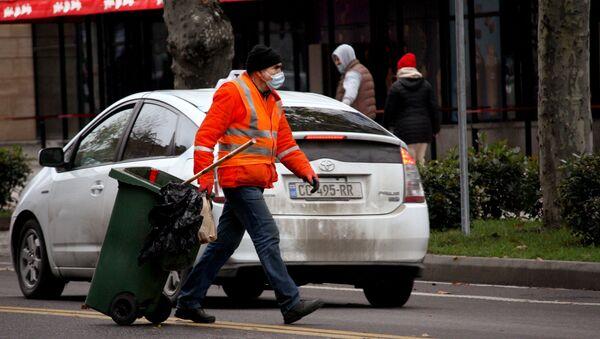 Работа во время пандемии - дворник в маске убирает улицы - Sputnik Грузия