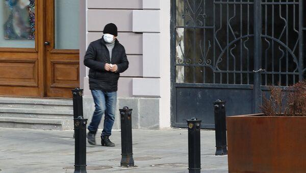 Эпидемия коронавируса - мужчина в маске зимой идет по улице - Sputnik Грузия