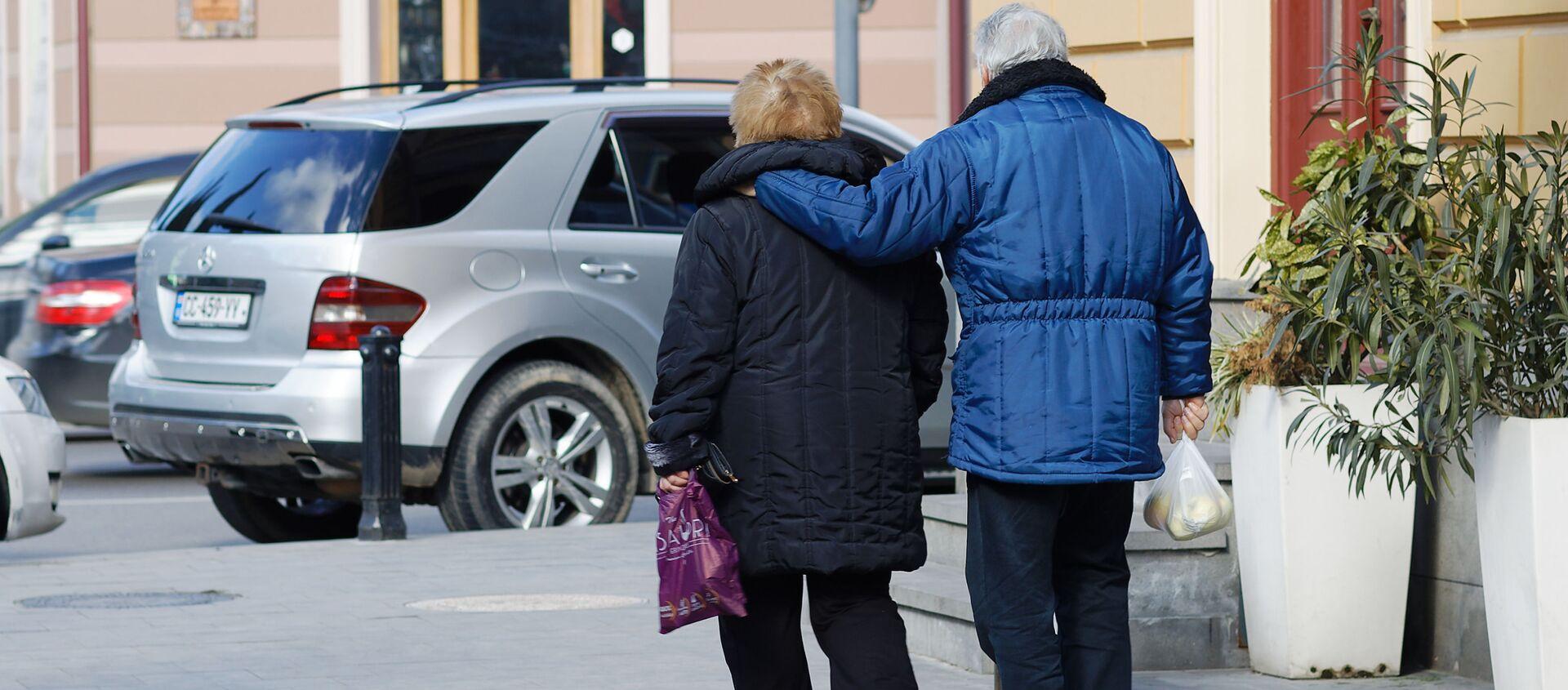 Пожилая семейная пара идет по улице с покупками - Sputnik Грузия, 1920, 06.02.2021