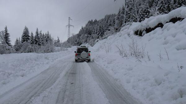Горная дорога в снегу - машина едет среди снежных сугробов - Sputnik Грузия