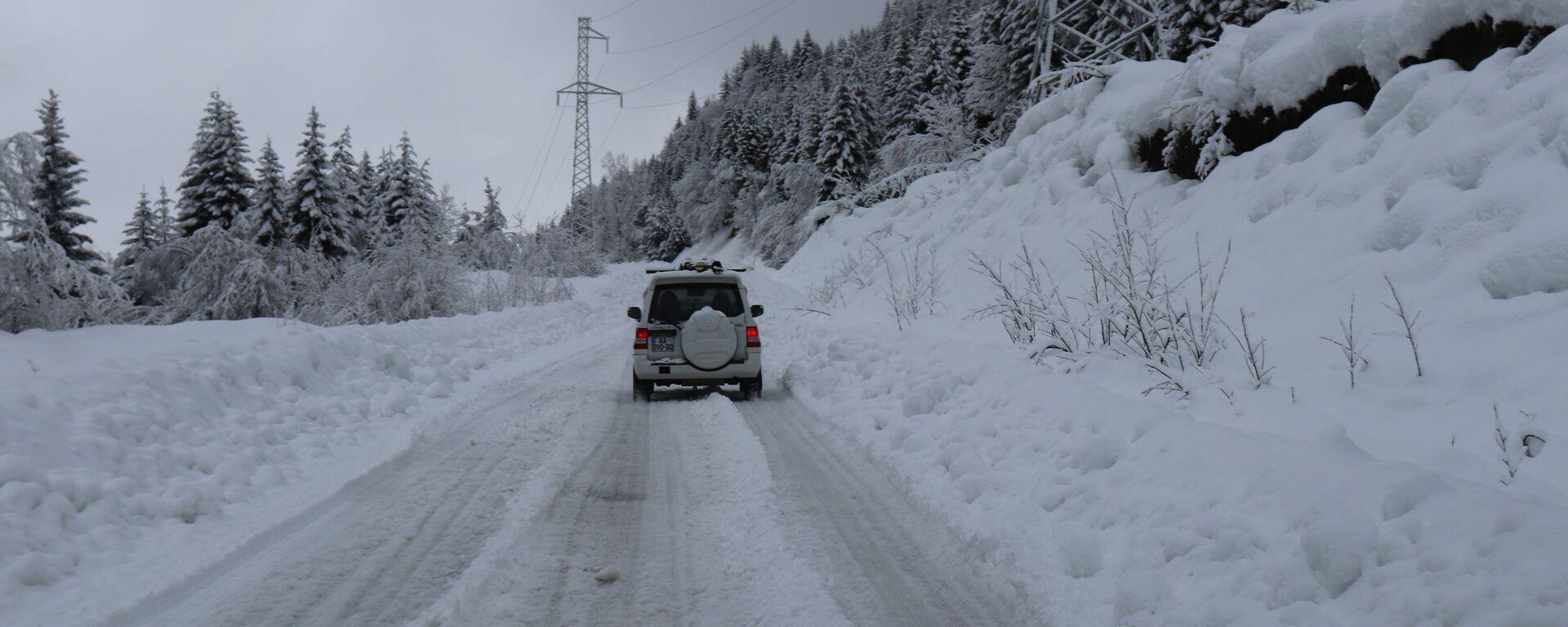 Горная дорога в снегу - машина едет среди снежных сугробов - Sputnik Грузия, 1920, 25.01.2021