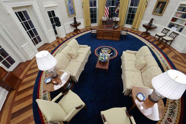 Президент-демократ Джо Байден вернул в Овальный кабинет золотистые шторы и синий ковер, которые появились здесь впервые при Билле Клинтоне. Как и многие предшественники, он сохранил стол, изготовленный еще в 1880 году из древесины корабля Резолют. Также, на столе появилась кружка и коробка с ручками - Sputnik Грузия