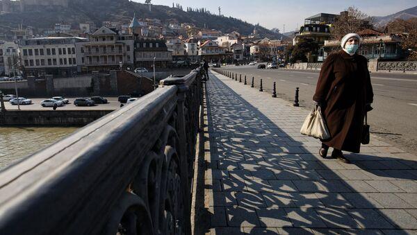 Вид на город Тбилиси - пожилая женщина в маске идет по Метехскому мосту - Sputnik Грузия