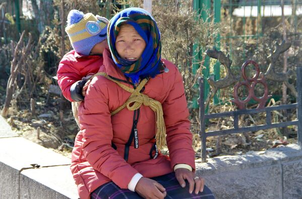 Женщина с ребенком на одной из улиц города Лхаса в Тибете - Sputnik Грузия