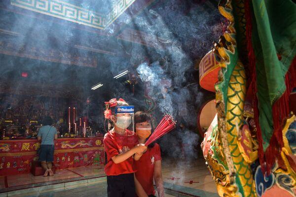 Девочки в защитных масках с ароматическими палочками во время празднования Нового года по лунному календарю в одном из храмов Индонезии - Sputnik Грузия