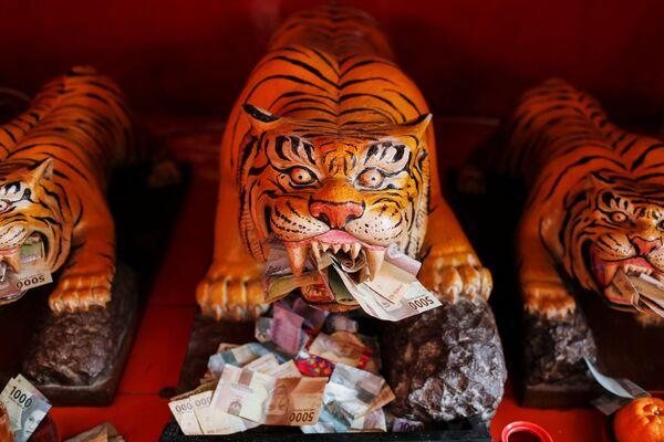Банкноты у скульптур тигров в храме Дхарма Бхакти во время празднования Нового года по лунному календарю в Джакарте - Sputnik Грузия