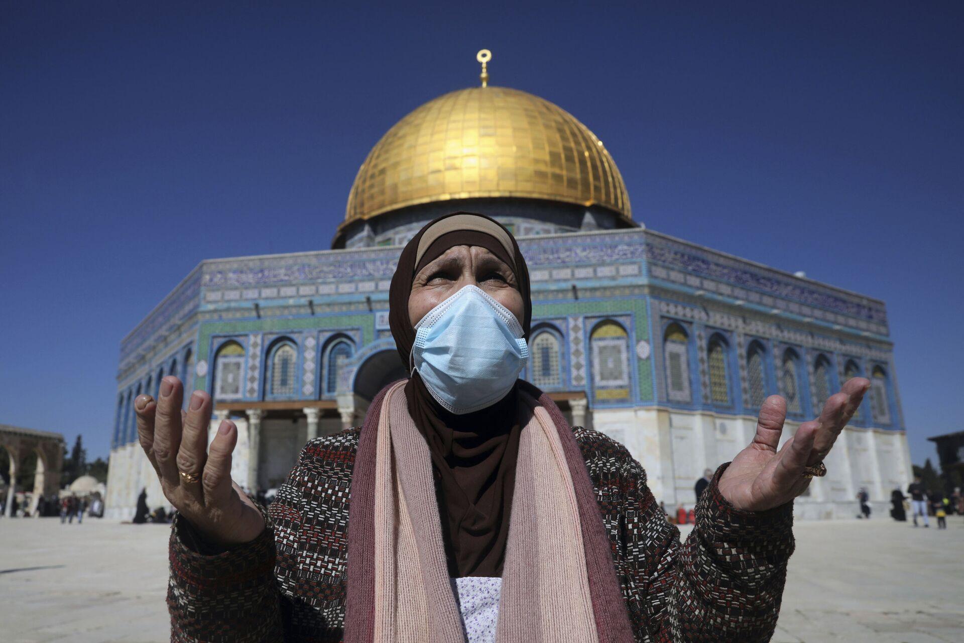 Пандемия коронавируса COVID и ислам. Женщина молится у мечети Аль-Акса в Иерусалиме - Sputnik Грузия, 1920, 13.10.2021