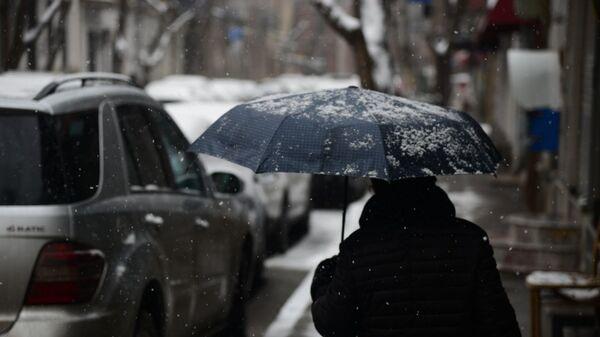 Снегопад в столице Грузии - женщина с зонтом идет по улице в снег - Sputnik Грузия